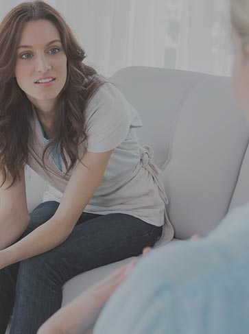 A female seating on a sofa listening carefully to a therapist