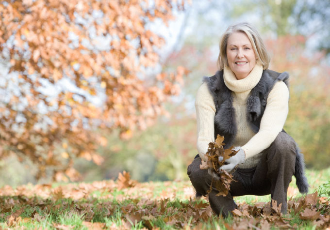A mature lady gathering fallen tree leaves