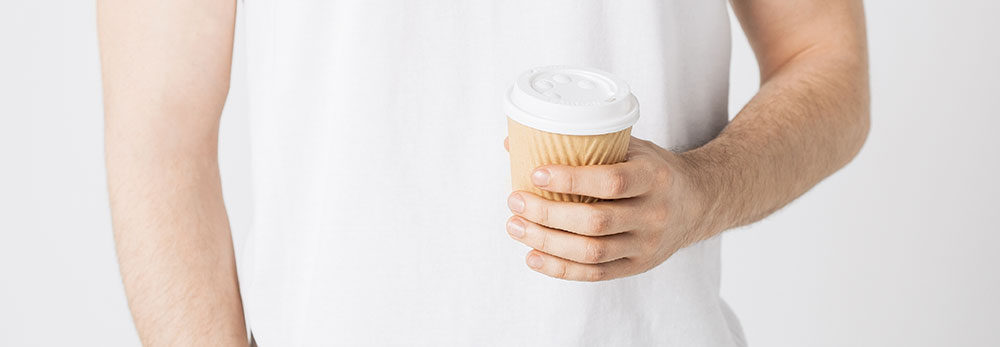 A male holding a coffee cup
